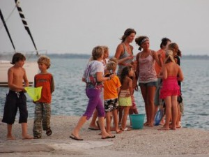 kinderen (groot en klein) vermaken zich in de haven